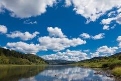 Blauer Himmel mit weißen Wolken über einem Gebirgsklaren Fluss stockbild