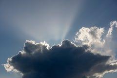 Blauer Himmel mit weißen Wolken in den Strahlen der Sonne lizenzfreie stockbilder