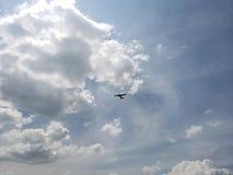 blauer Himmel mit weißen Wolken und das Schattenbild eines Flugzeuges stockbild