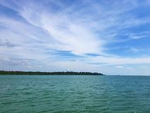 Blauer Himmel mit Wolke und grünes Meer mit Insel stockbild