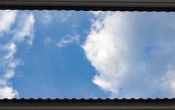 Blauer Himmel mit Wolke zwischen Dach Lizenzfreie Stockfotos