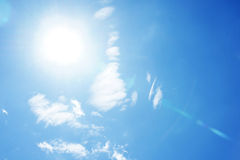 Blauer Himmel mit Wolken und Sonne Lizenzfreie Stockbilder
