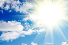 blauer Himmel mit Wolken und Sonne mit Strahlen des Lichtes Lizenzfreie Stockfotos