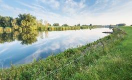 Blauer Himmel und Bäume reflektiert im Fluss Stockfotografie
