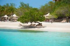 Blauer Himmel und Klubsessel der tropischen Ferien auf weißem Sand setzen auf den Strand Stockfotografie