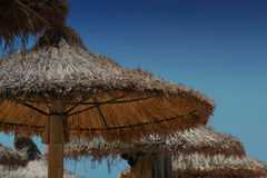 Blauer Himmel und Regenschirme auf dem Strand lizenzfreie stockfotografie
