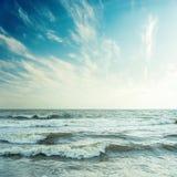 Blauer Himmel und stürmisches Meer im Sonnenuntergang Stockfotografie