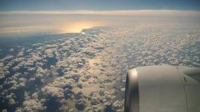 Blauer Himmel und weiße flaumige Wolkenansicht von oben durch das Fenster des Flugzeuges bei Sonnenaufgang stock footage