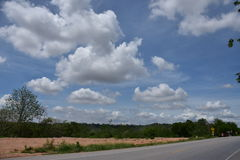 Blauer Himmel und weiße Wolken auf Landstraße in Thailand Stockfoto