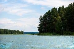 Blauer Himmel und weiße Wolken, grüner Wald und blaues Wasser von Fluss Stockfotografie
