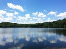 Blauer Himmel und Wolken über See Lizenzfreies Stockfoto