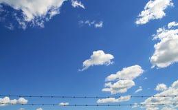Blauer Himmel und Wolken mit Barbwire Stockfotos
