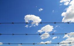 Blauer Himmel und Wolken mit Barbwire stockfotografie
