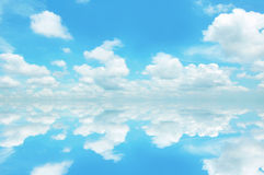 Blauer Himmel und Wolken mit Reflexion auf Meerwasser Stockfotografie