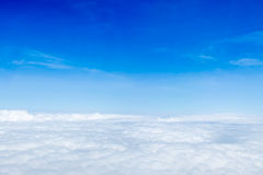 Blauer Himmel und Wolkenspitzeansicht vom Flugzeugfenster, Natur backgrou Lizenzfreies Stockbild