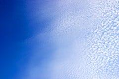 Blauer Himmel-Vignette mit punktierten gebrochenen Wolken Lizenzfreie Stockbilder