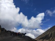 Blauer Himmel, weiße starke Wolke, Berg, Pferde und Bergsteiger stockbild