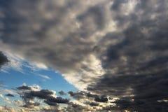 Blauer Himmel weit weg durch die grauen und weißen Wolken des Sturms stockfotografie
