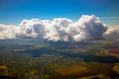 Blauer Himmel, Wolken und Erdsichtbares durchgehendes sie von einem flachen Fenster stockbild