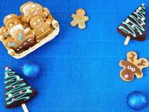 Blauer Hintergrund des neuen Jahres Weihnachtsdekorationen, Lebkuchenmänner und Honigkuchen gestalten Lizenzfreie Stockfotografie