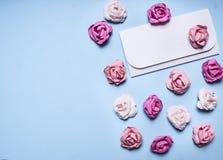 blauer Hintergrund des weißen Umschlags mit bunter Papierrosengrenze, Platz für Textdekorationen für Clo Draufsicht des Valentins Stockfotografie