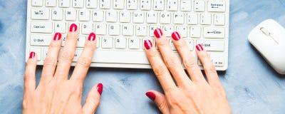 Blauer Hintergrund mit Frau ` s Hand und Tastatur Stockbilder