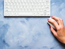 Blauer Hintergrund mit Frau ` s Hand und Tastatur Stockfoto