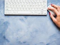 Blauer Hintergrund mit Frau ` s Hand und Tastatur Lizenzfreie Stockbilder