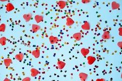 Blauer Hintergrund mit kleinen mehrfarbigen und großen roten Herzen lizenzfreie stockfotografie