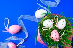 Blauer Hintergrund Ostern, auf dem Gras Ostereier im Fr?hjahr mit rosa B?ndern verziert werden stockbild