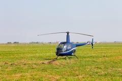 Blauer Hubschrauber auf Feld Lizenzfreie Stockfotografie