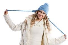 Blauer Hut auf einem blonden Mädchen, Flechten des Hutes spielend Lizenzfreie Stockfotos