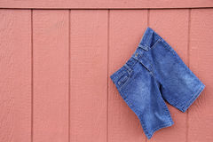 Blauer Jean Capri Shorts auf roter Wand lizenzfreie stockfotografie