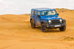 Blauer Jeep Wrangler Rubicon Unlimited an den WüstenSanddünen Lizenzfreie Stockfotos