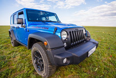 Blauer Jeep Wrangler Rubicon Unlimited im wilden Tulpenfeld nahe Salzwasserreservoirsee Manych-Gudilo Stockbild