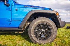 Blauer Jeep Wrangler Rubicon Unlimited im wilden Tulpenfeld nahe Salzwasserreservoirsee Manych-Gudilo Stockfotografie