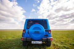 Blauer Jeep Wrangler Rubicon Unlimited im wilden Tulpenfeld nahe Salzwasserreservoirsee Manych-Gudilo Lizenzfreie Stockfotografie