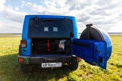 Blauer Jeep Wrangler Rubicon Unlimited im wilden Tulpenfeld nahe Salzwasserreservoirsee Manych-Gudilo Stockbilder