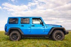 Blauer Jeep Wrangler Rubicon Unlimited im wilden Tulpenfeld nahe Salzwasserreservoirsee Manych-Gudilo Lizenzfreies Stockfoto