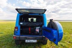 Blauer Jeep Wrangler Rubicon Unlimited im wilden Tulpenfeld nahe Salzwasserreservoirsee Manych-Gudilo Lizenzfreies Stockbild
