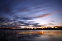 Blauer kalter Sonnenaufgang über See Stockfoto