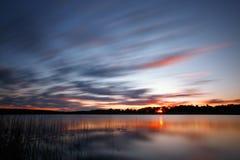 Blauer kalter Sonnenaufgang über See Stockfotos
