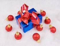 Blauer Kasten mit rotem Bogen und roten Kugeln Stockfotografie