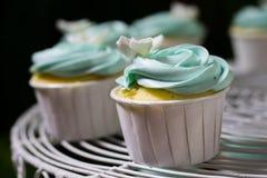 Blauer kleiner Kuchen auf cakestand gegen dunklen Hintergrund, Nahaufnahme Stockfotografie