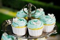Blauer kleiner Kuchen auf cakestand gegen dunklen Hintergrund, Nahaufnahme Stock Abbildung