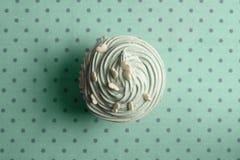 Blauer kleiner Kuchen mit Schlagsahne und Herz besprüht auf punktiertem b Stockfotografie