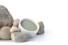 Blauer kosmetischer Lehm mit Steinen auf einem weißen Hintergrund Stockbild