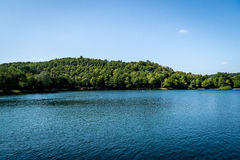 Blauer Kristallsee, Wald und klarer Himmel Stockbilder