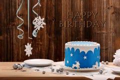 Blauer Kuchen des Geburtstages auf dem hölzernen Hintergrund Stockbild