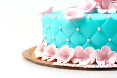 Blauer Kuchen mit den rosafarbenen Blumen lokalisiert Lizenzfreies Stockbild